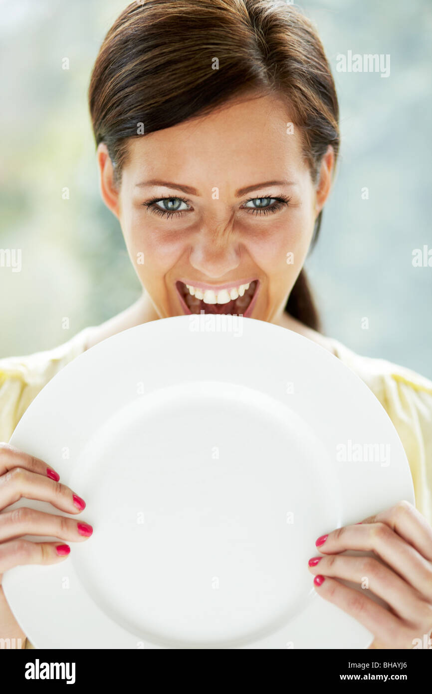 Girl biting plate - Stock Image