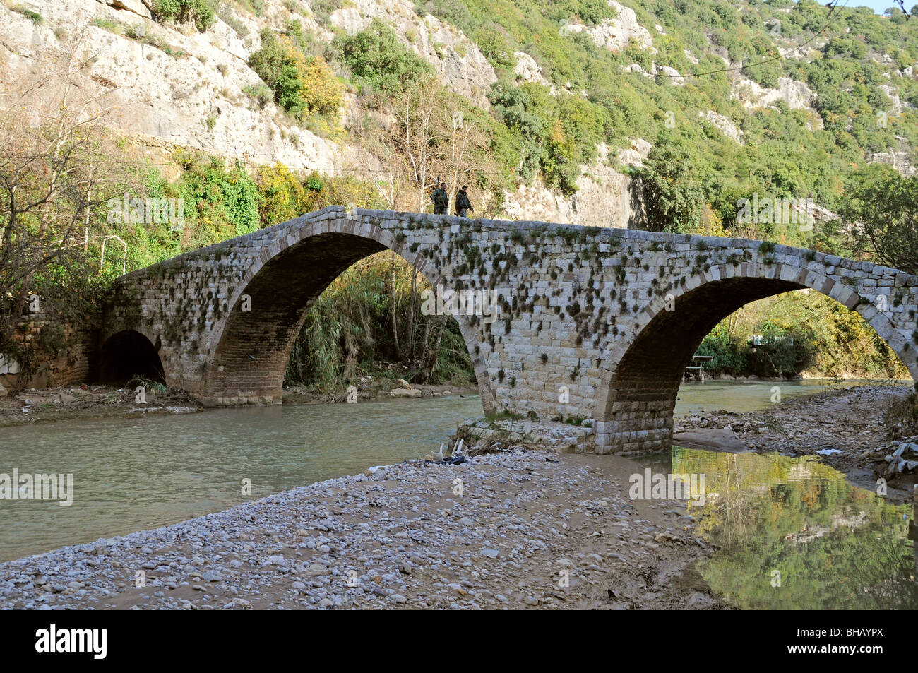 Two Lebanese army soldiers on patrol atop an old arched Mamluk era stone bridge above the  Dog River (Nahr al Kalb), - Stock Image
