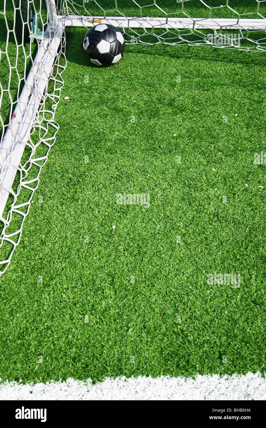 Football in back corner of net after goal Stock Photo