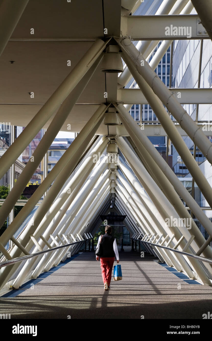 Woman walking through glass triangle shaped walkway in downtown Portland, Oregon, USA - Stock Image