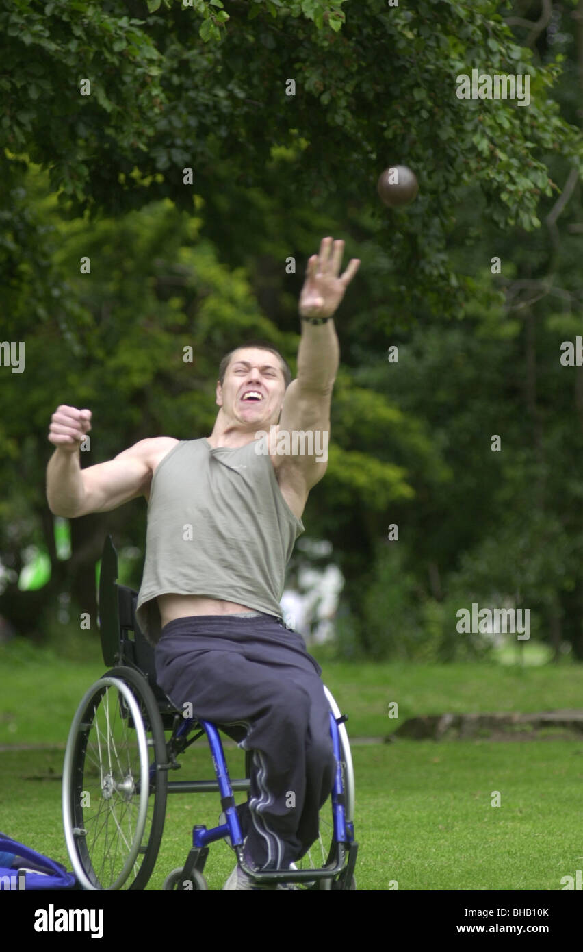 Young white disabled  man practices shot putting UK - Stock Image