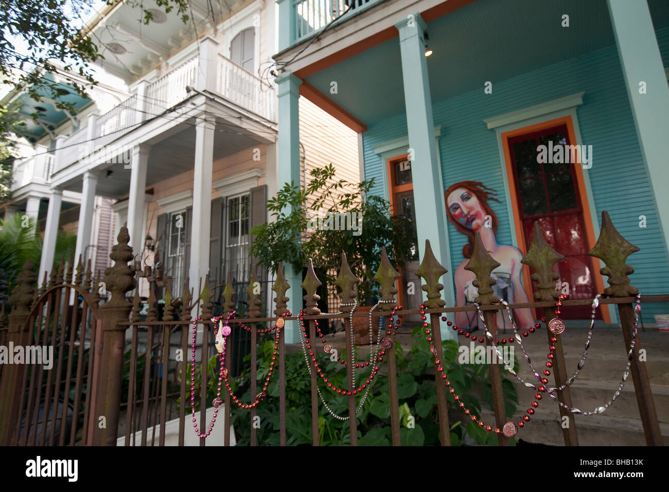 House with artwork on porch and Mardi Gras beads on iron fence on Magazine Street, New Orleans, Louisiana. - Stock Image
