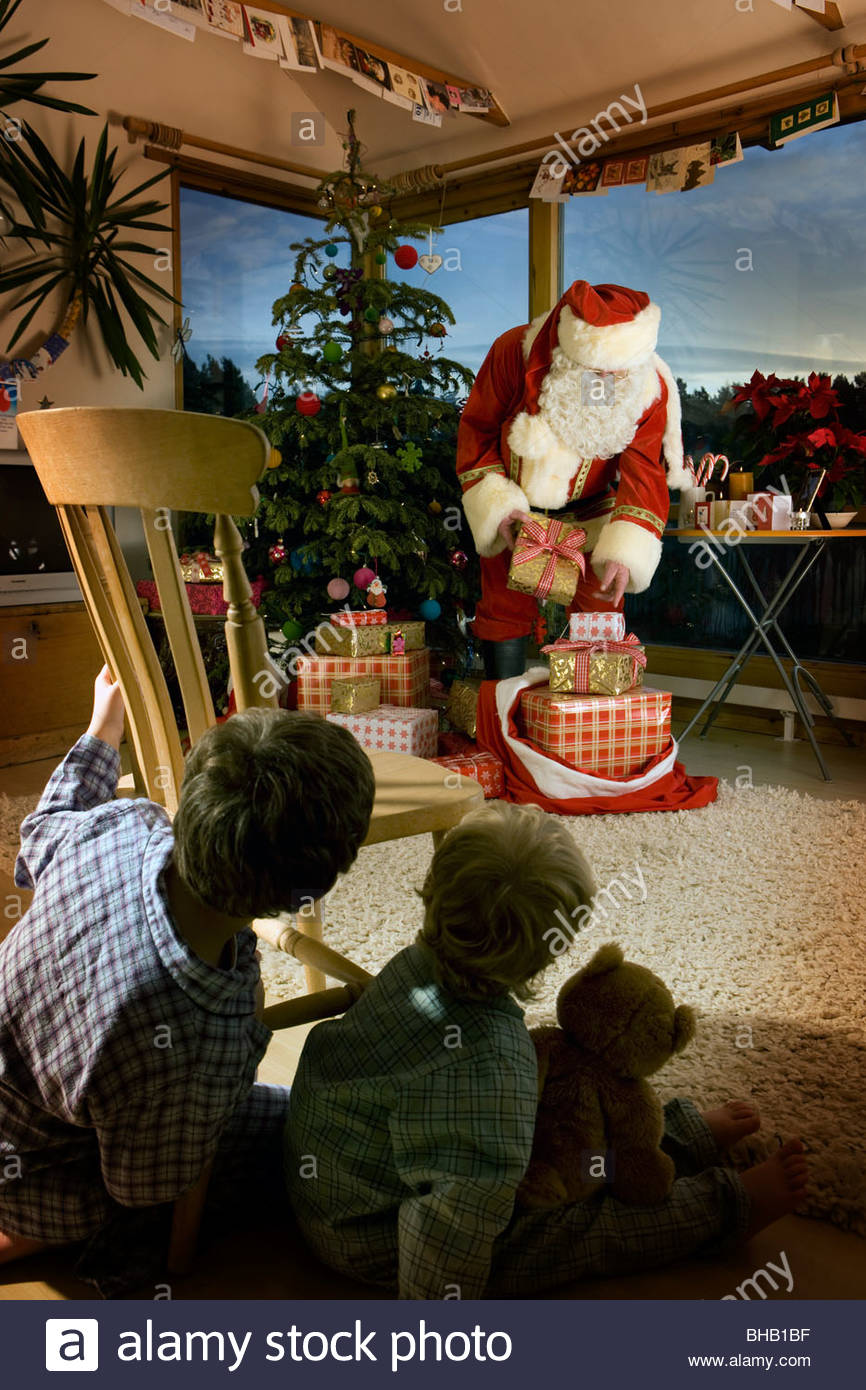 Boys watching Santa deliver Christmas gifts in living room - Stock Image