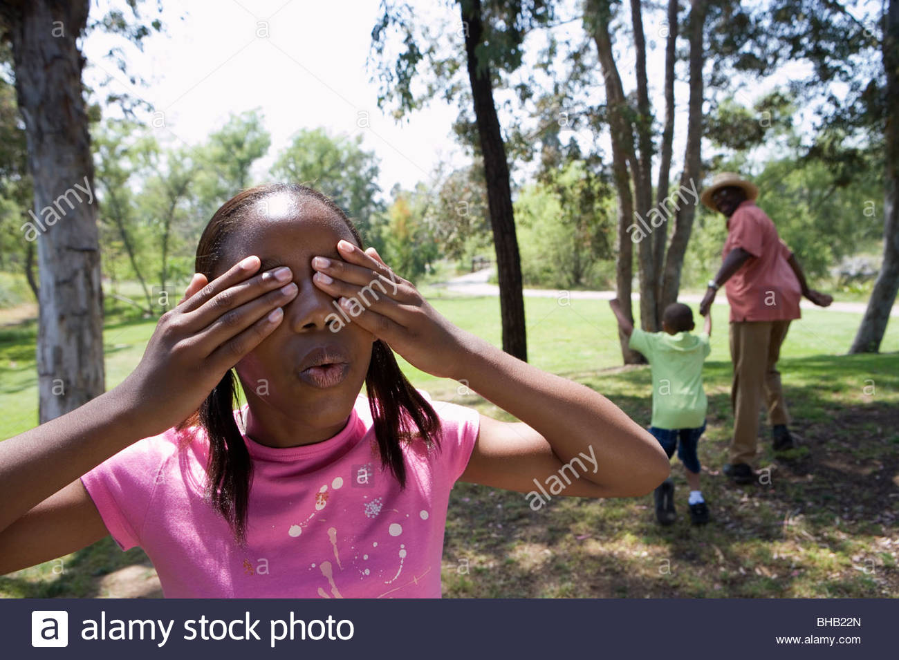Senior man playing hide and seek with grandchildren (6-10) in park, girl covering eyes in foreground - Stock Image