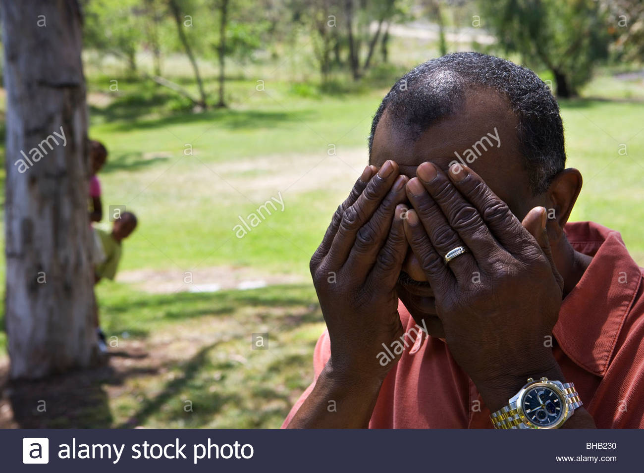 Children (6-10) playing hide and seek with grandfather in park, senior man covering eyes - Stock Image