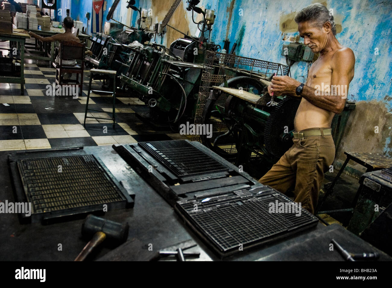 A Cuban master printer, leant against a printing machine, waiting for a new load in the print shop, Santiago de - Stock Image