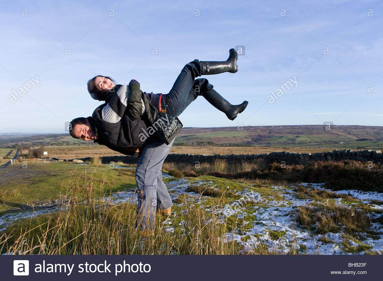 Playful couple in rural field - Stock Image