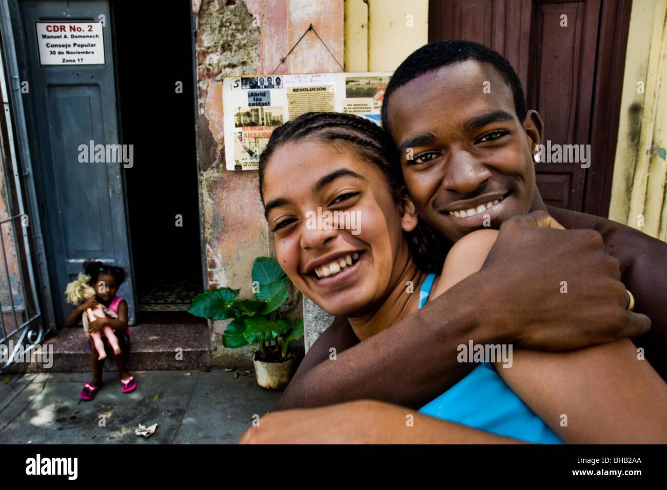 A young Cuban boy embracing a girl on the street of Santiago de Cuba, Cuba. - Stock Image