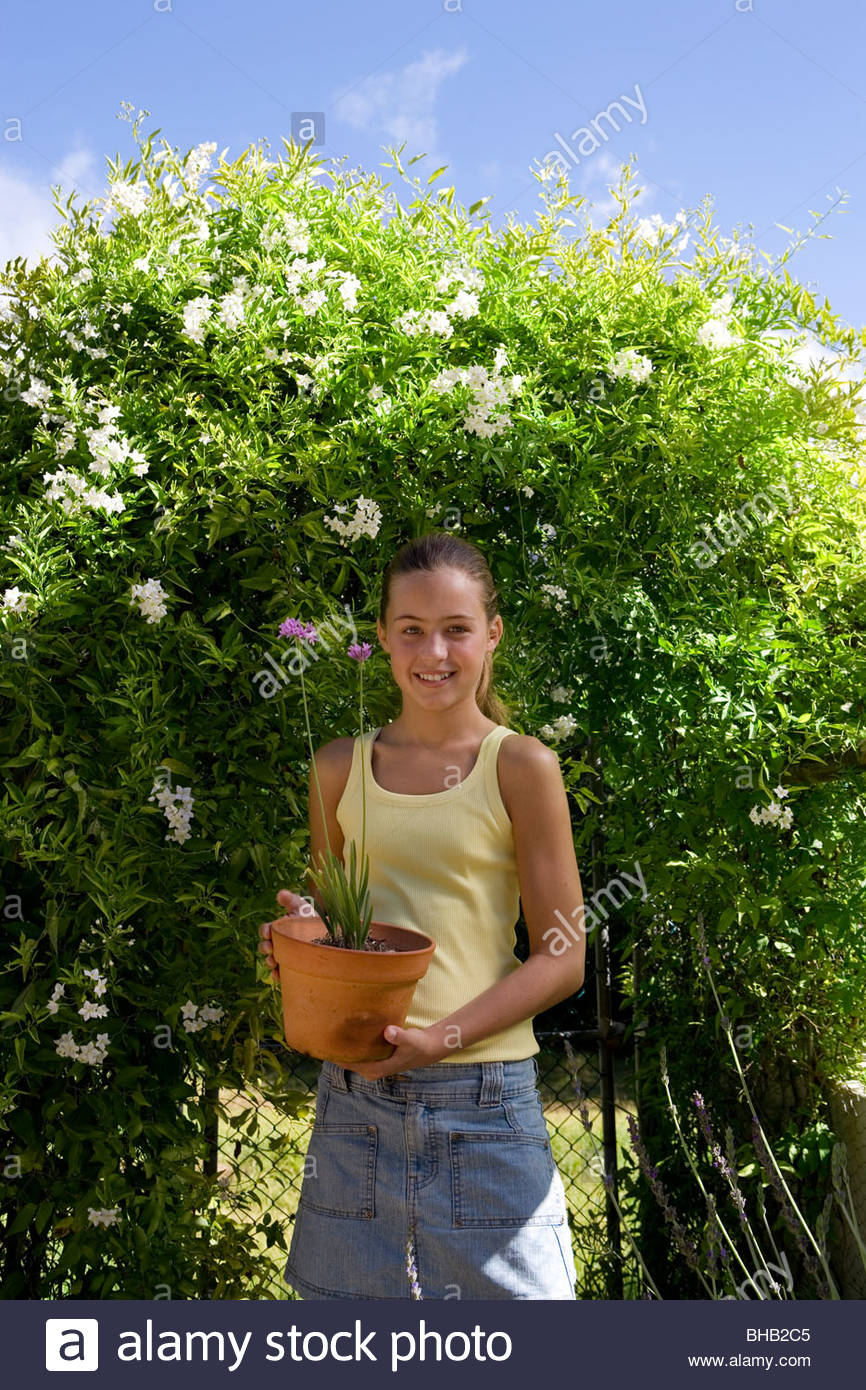 Girl (10-12) with flower pot by hedge, smiling, portrait - Stock Image