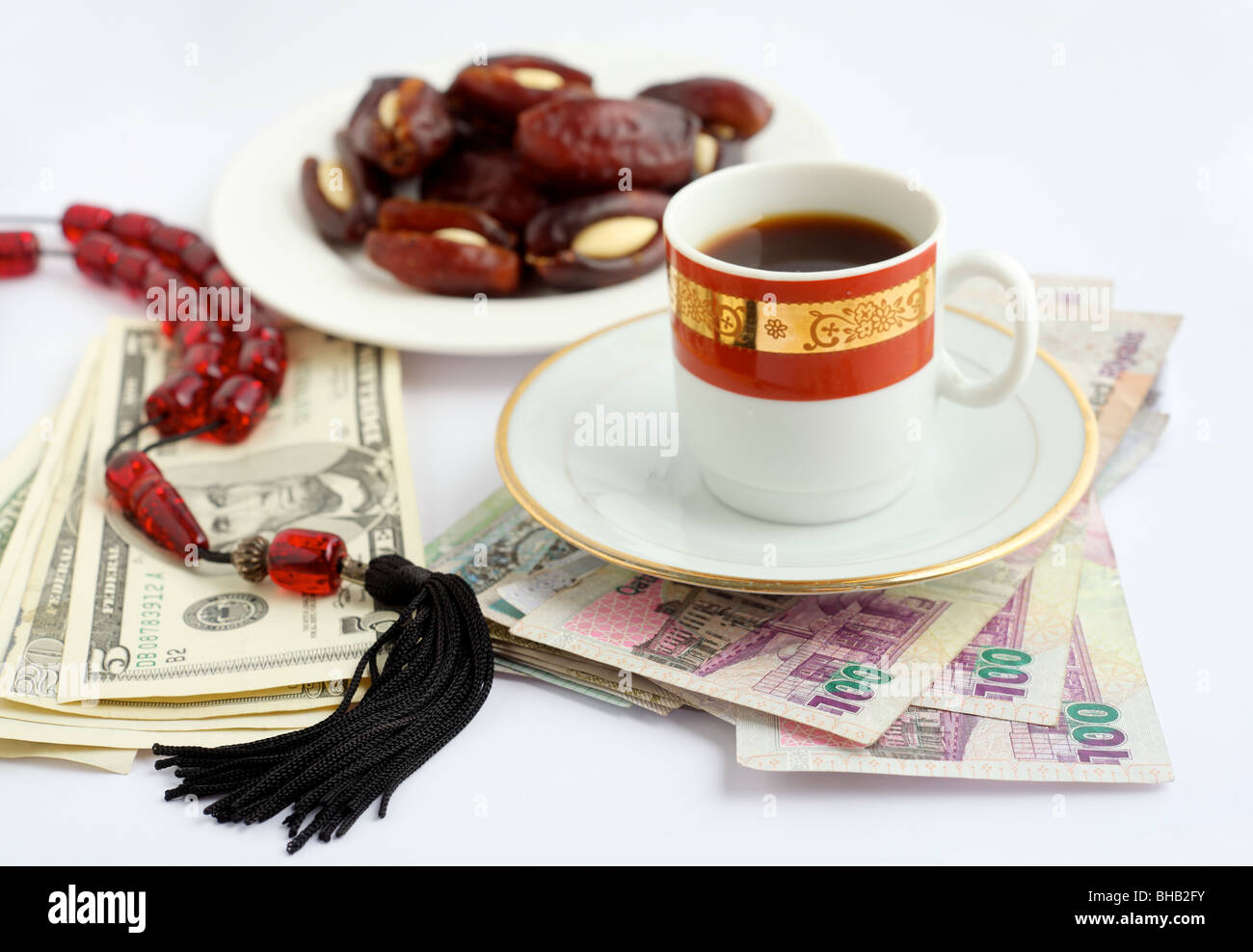 Coffee, dates stuffed with almonds and worry beads, on piles of Qatari Arab money and US dollars. Stock Photo
