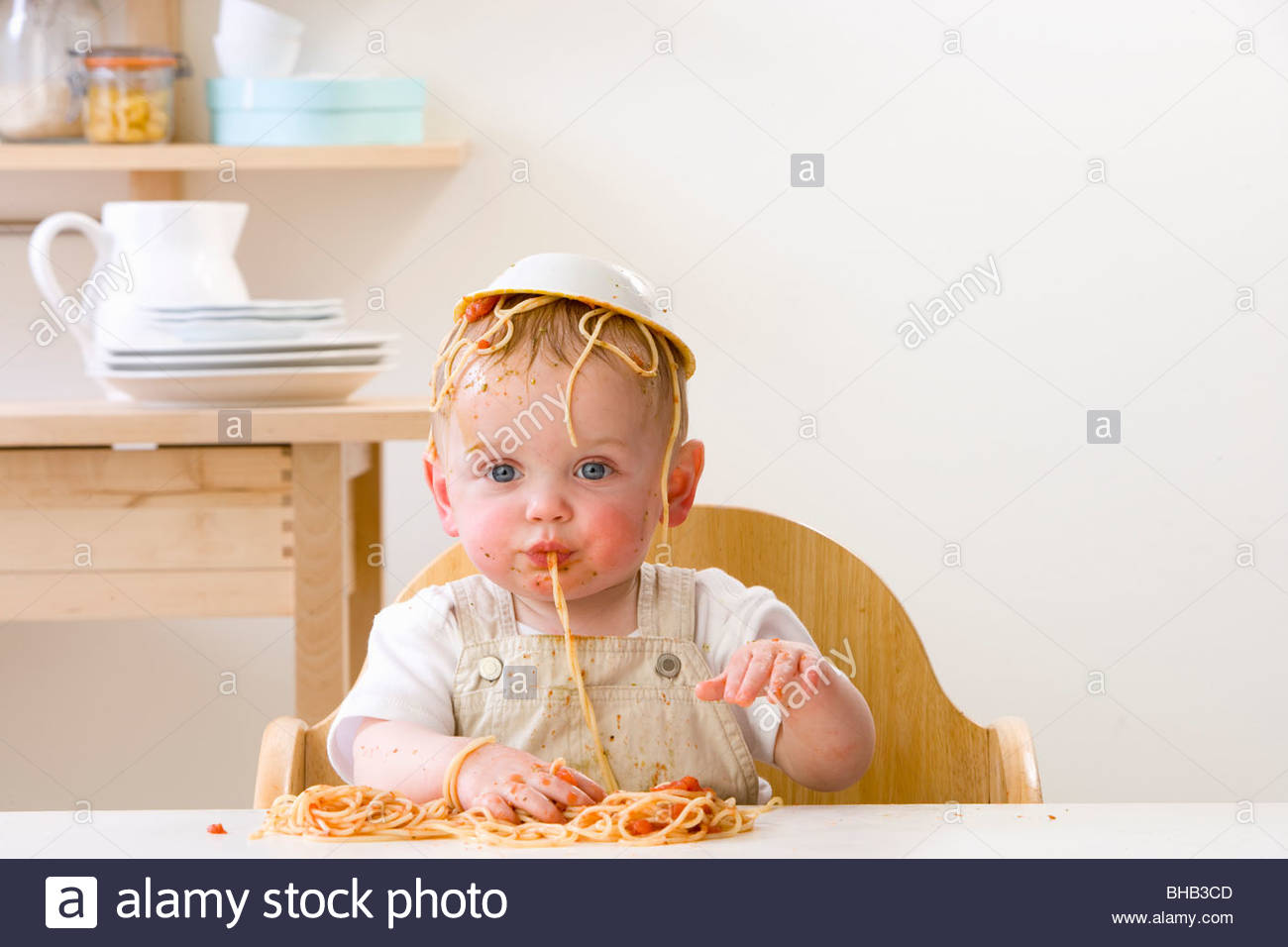 Messy baby boy in high chair with bowl of spaghetti on head - Stock Image