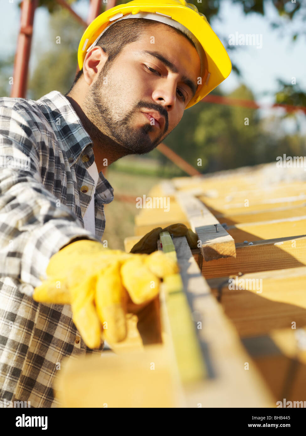 latin american construction worker on house roof with measuring tape. - Stock Image