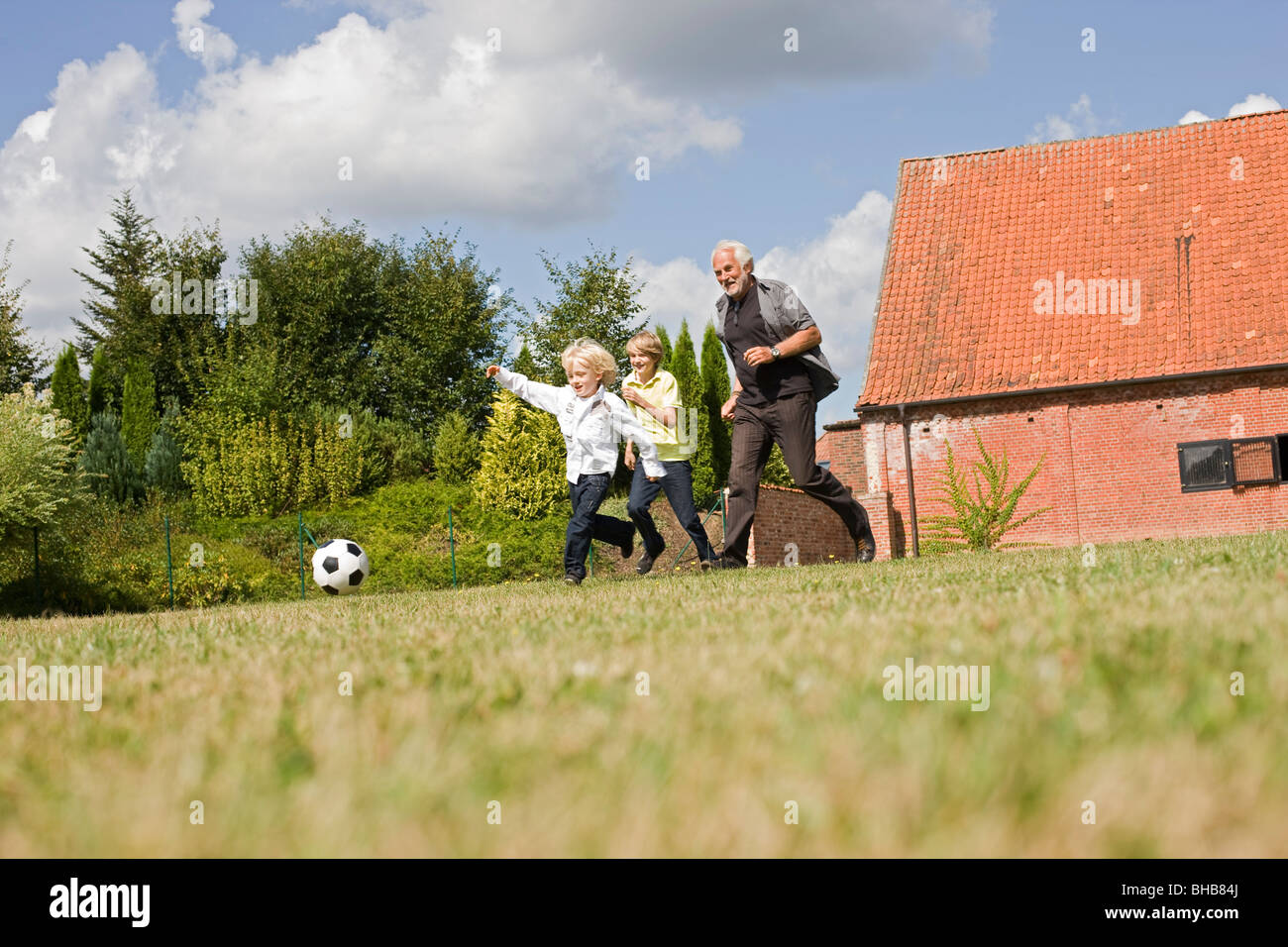 grandfather and kids playing football - Stock Image