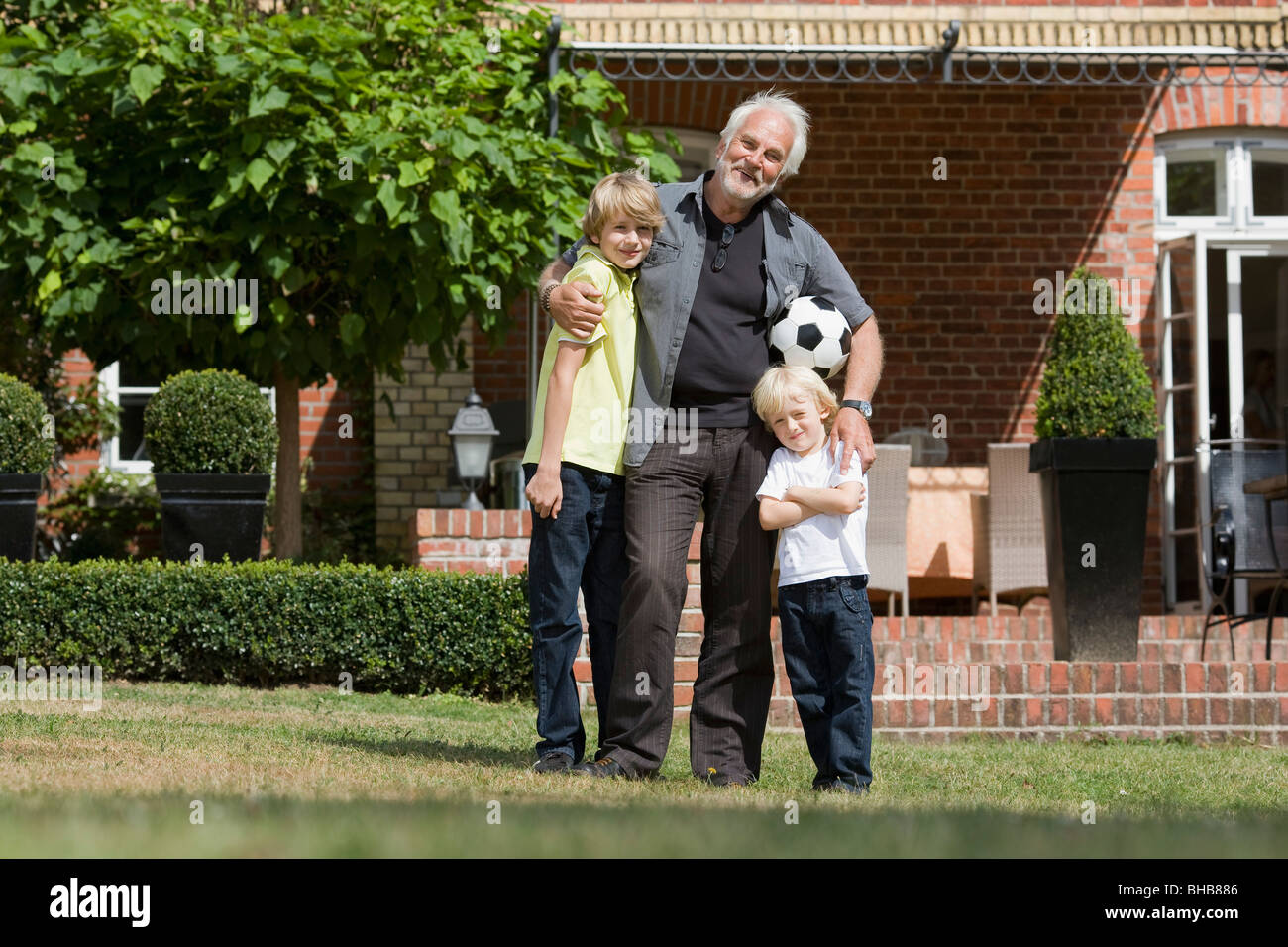 grandfather and kids with football - Stock Image