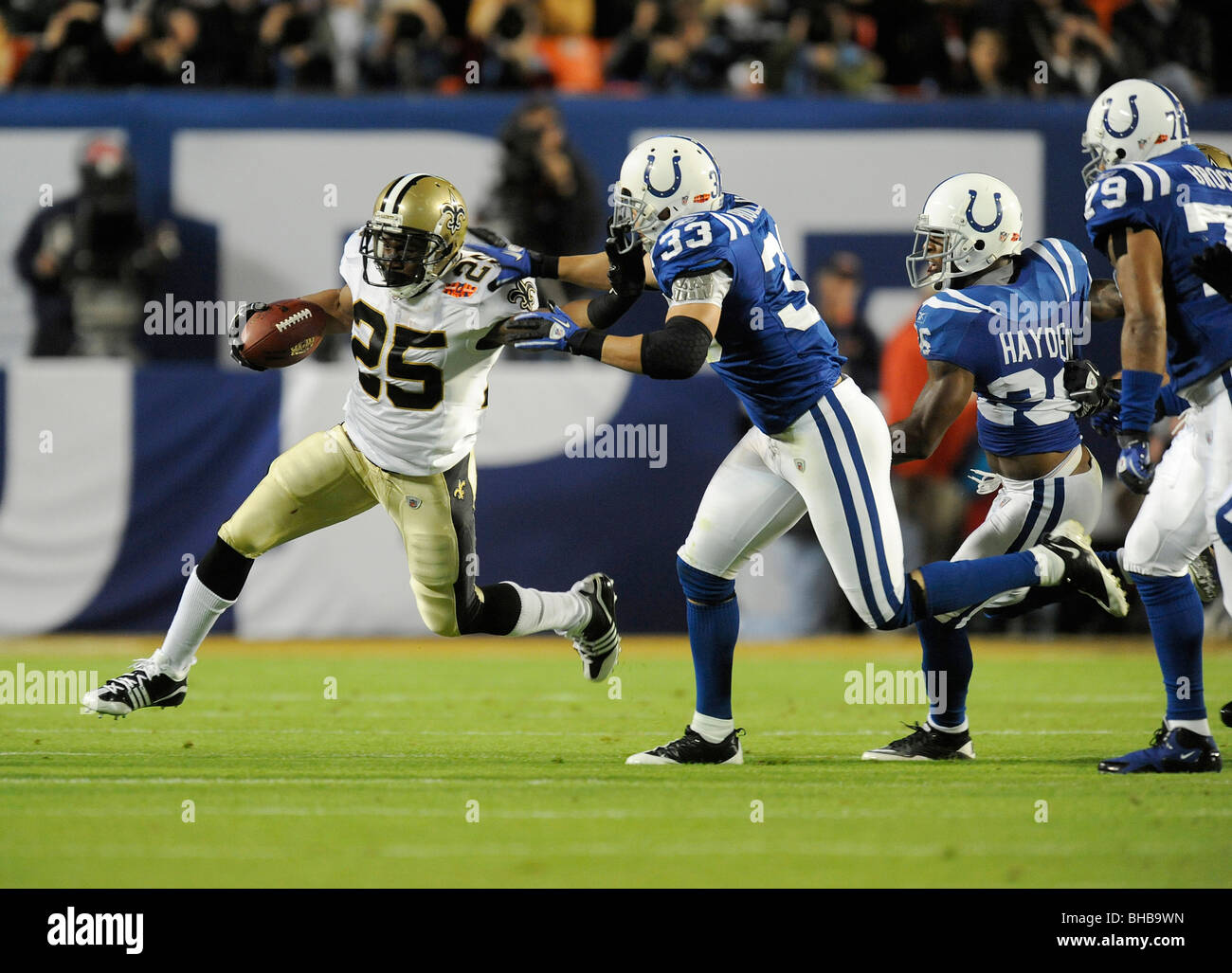 Reggie Bush #25 of the New Orleans Saints rushes as Melvin Bullitt #33 of the Indianapolis Colts defends in Super - Stock Image