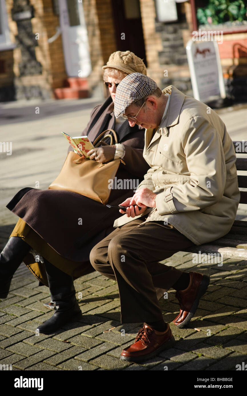 Elderly man entering contacts into his mobile phone as his wife reads them out from her address book, UK - Stock Image