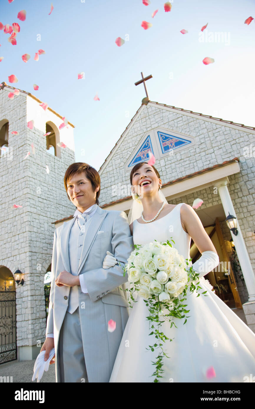 bride and groom with bouquet standing outside church, flower petals been thrown on them - Stock Image