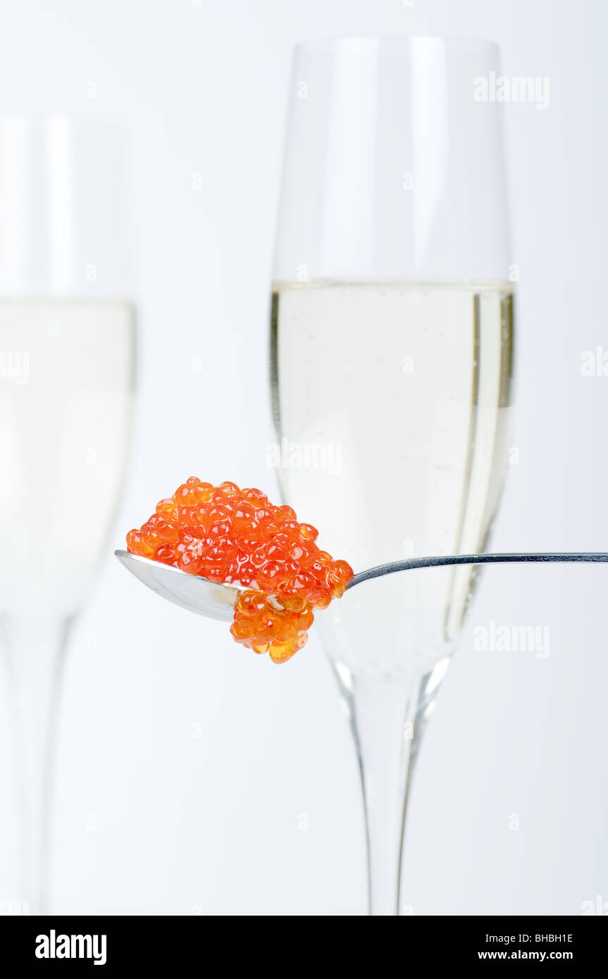 A  spoon with salmon caviar in front of full champagne glasses. Focus on caviar. - Stock Image