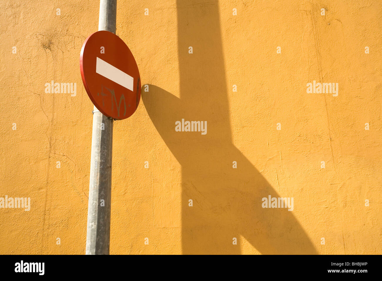 A red No Entry street sign stands next to an orange wall. The sign casts a shadow on the wall. - Stock Image