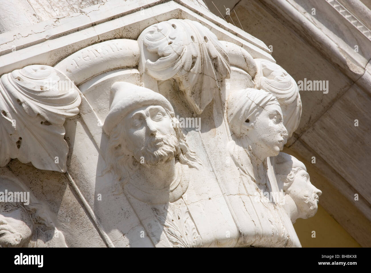 Venice, Veneto, Italy. Carved heads on one of the stone columns of the Palazzo Ducale. - Stock Image