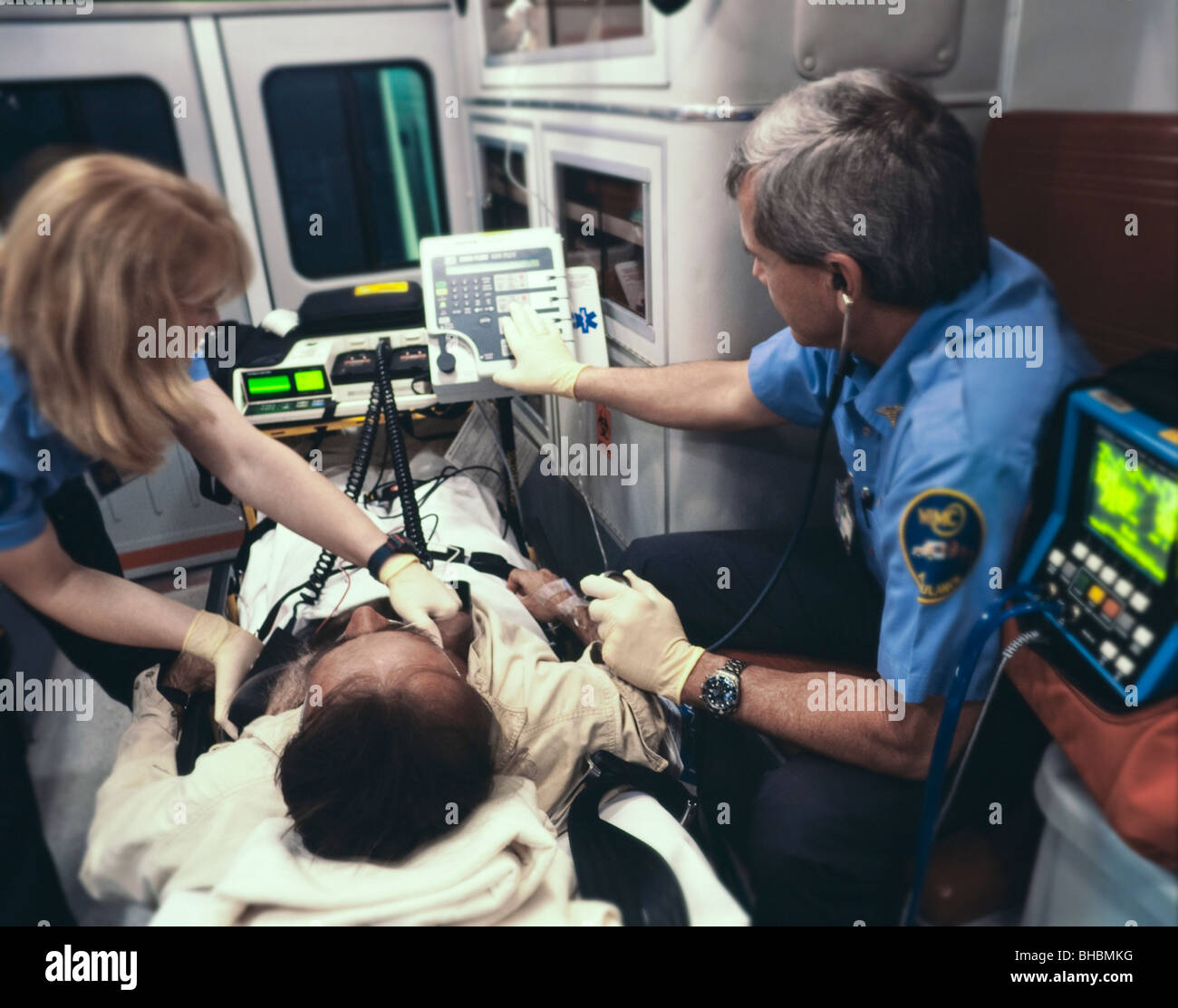 Paramedics with patient in ambulance - Stock Image