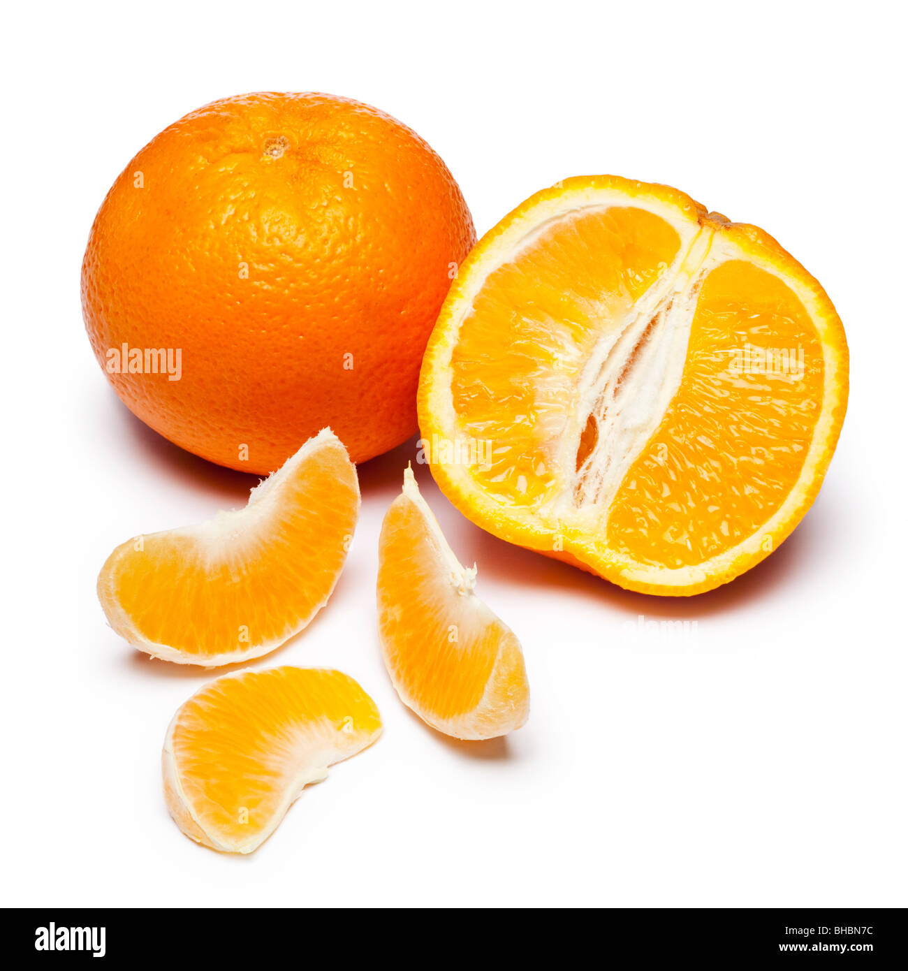 Oranges whole and halved with segments - Stock Image