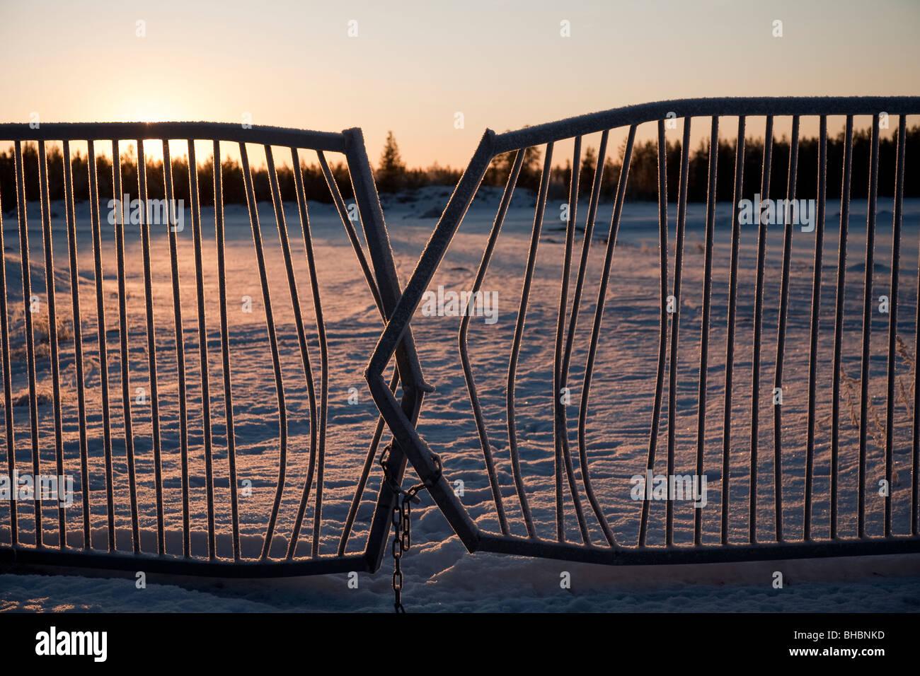 Vandalized broken metal gate against sun - Stock Image