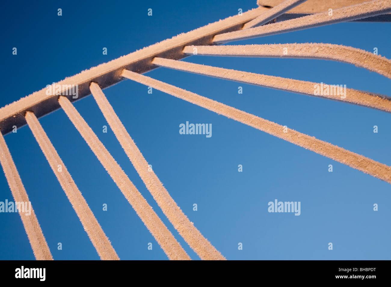 Frosty steel bars against blue sky - Stock Image