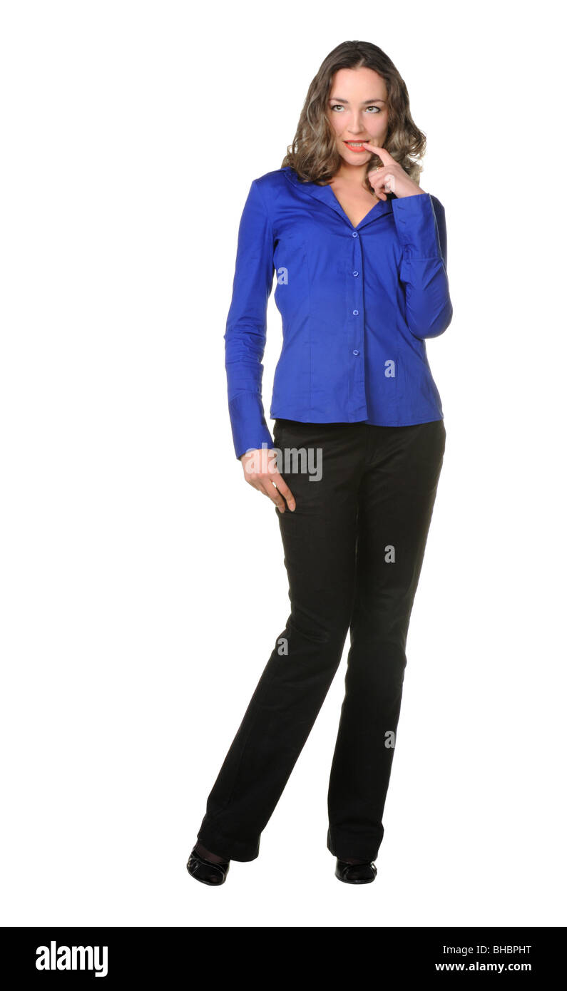 The attractive girl in trousers and dark blue shirt. The coquettish pose - has bitten an index finger - Stock Image