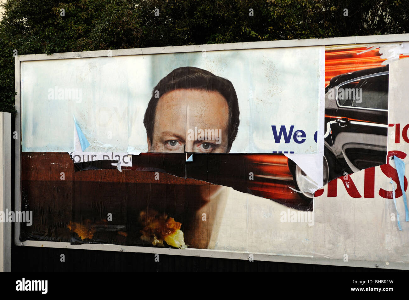 a billboard with a torn picture of David Cameron - Stock Image