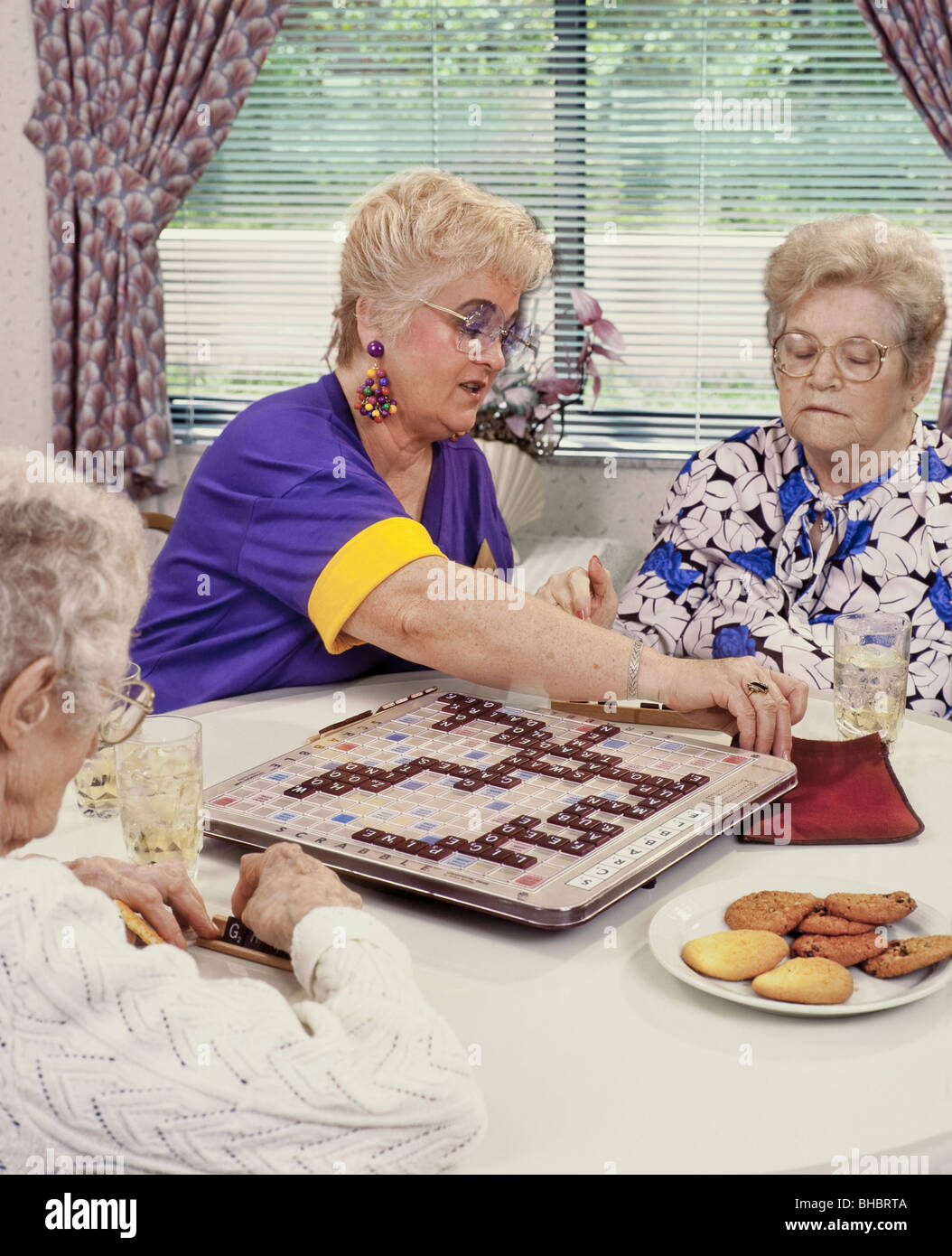 Senior aged women in assisted living facility playing board game - Stock Image