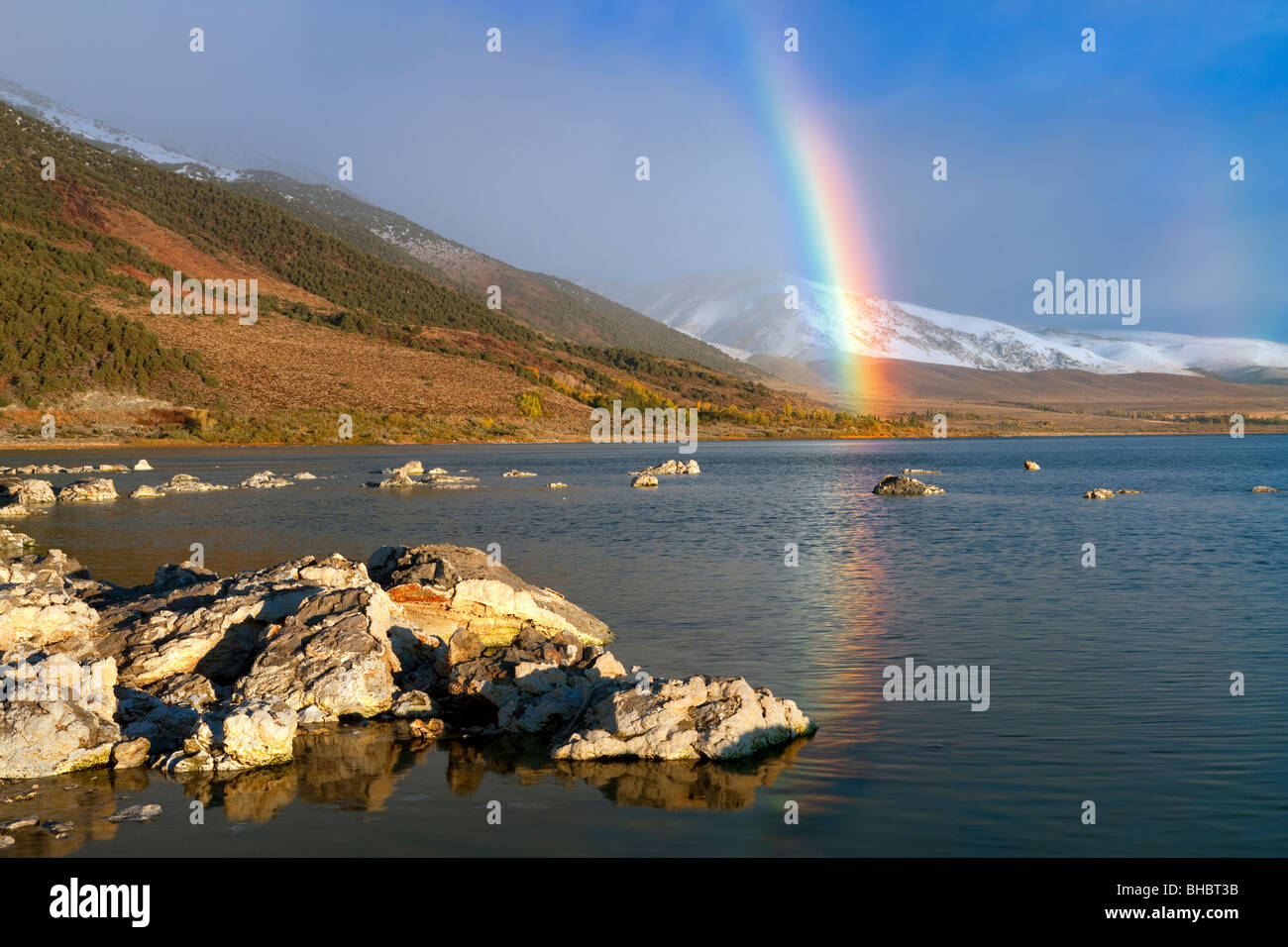 Rainbow with reflection and snow in mountains at Mono Lake. California. - Stock Image