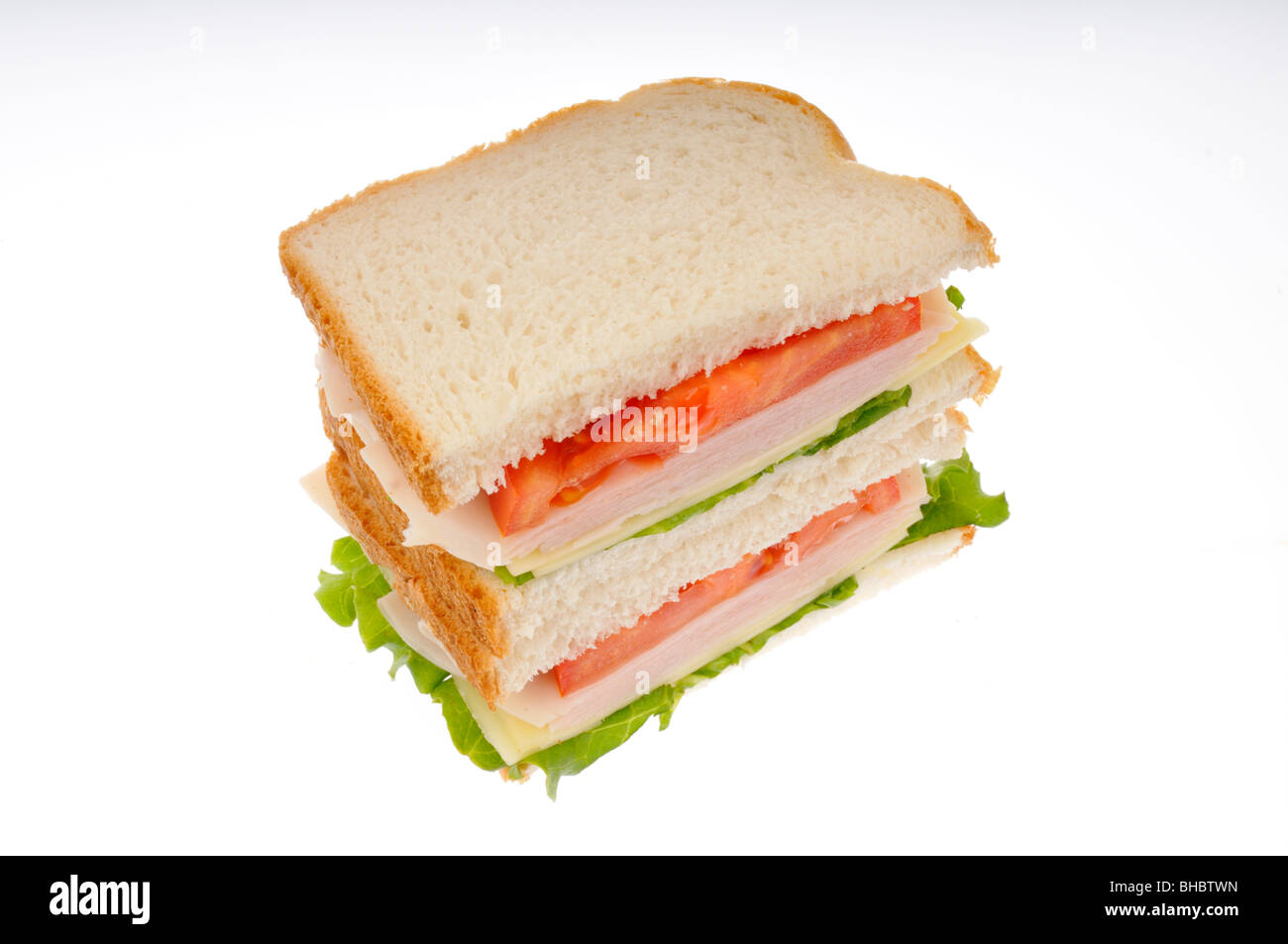turkey and cheese sandwiche cut in half on white bread with lettuce and tomato stacked on white background. cut - Stock Image