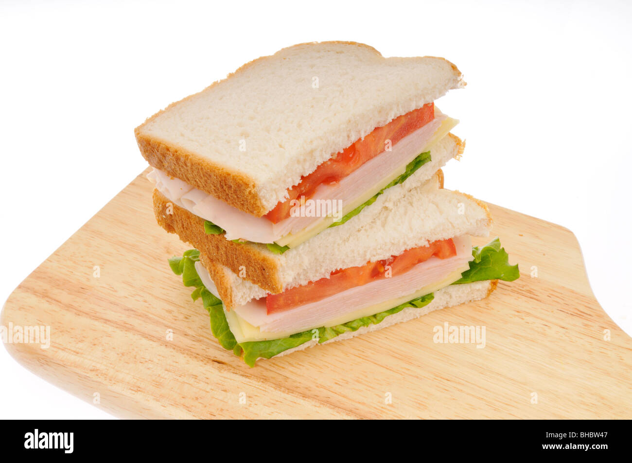 turkey and cheese sandwiche on white bread with lettuce and tomatoe stacked on a cutting board on white background. - Stock Image