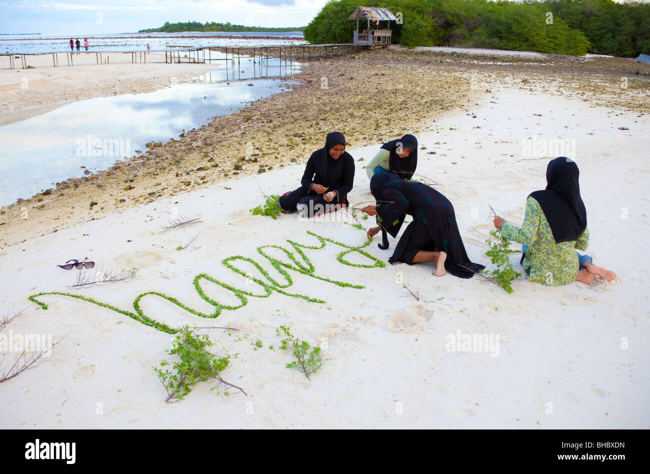 muslim young women writing on sand beach happy new year