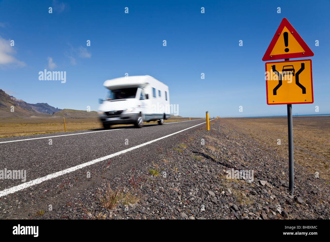Motion blurred photograph motor home or camper van driving on an open road with danger sign - Stock Image
