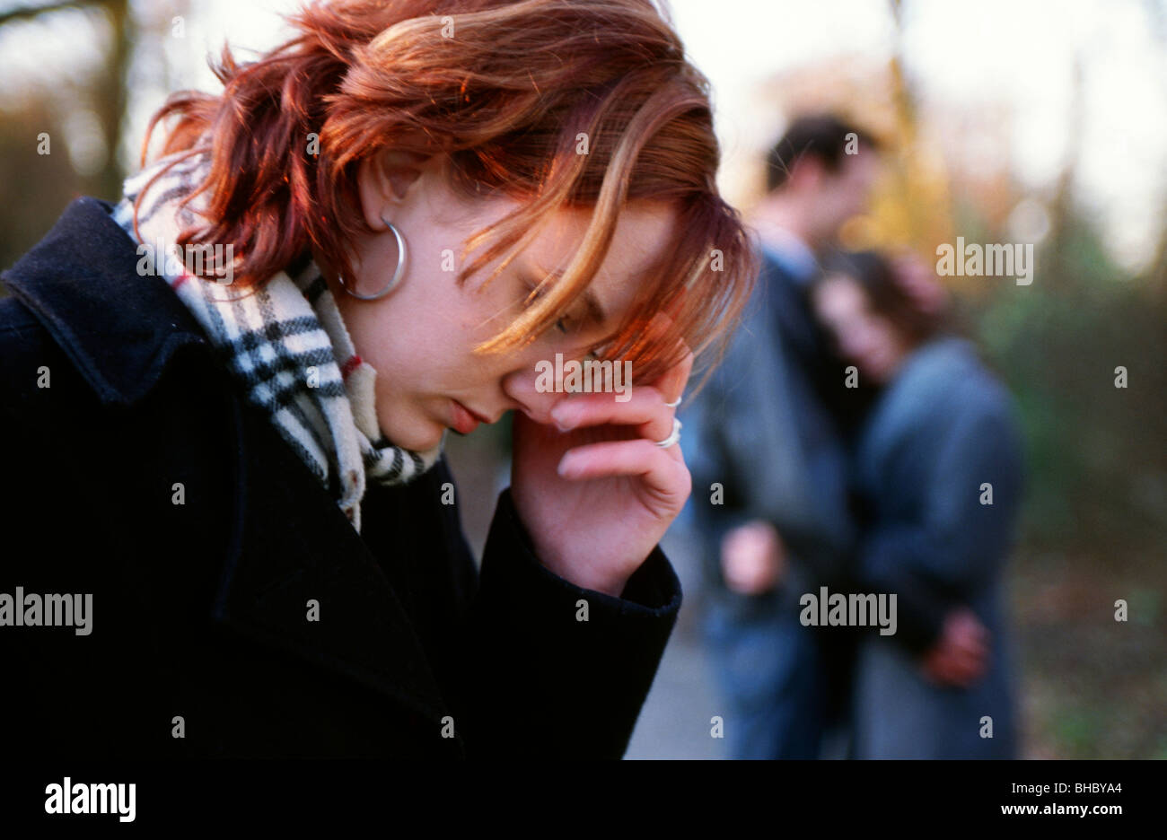 Heart broken  young woman outside and couple comforting in the background. - Stock Image