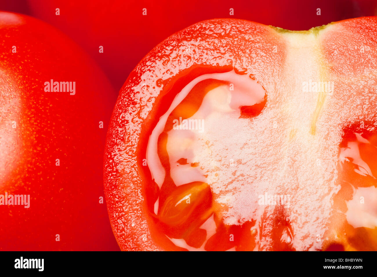 Ripe juicy red tomatoes whole and halved close up - Stock Image