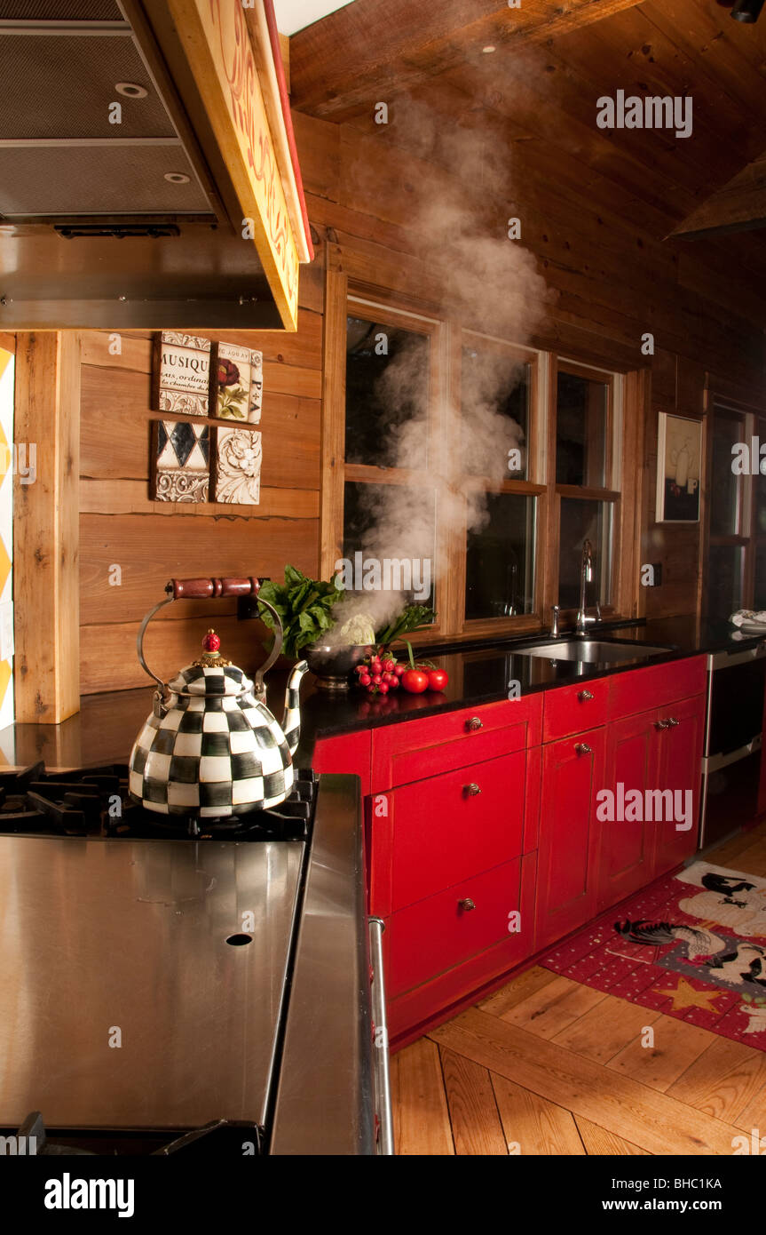 Vertical shot of cozy elegant wood kitchen with red counters and black counter tops and tea kettle spouting steam - Stock Image