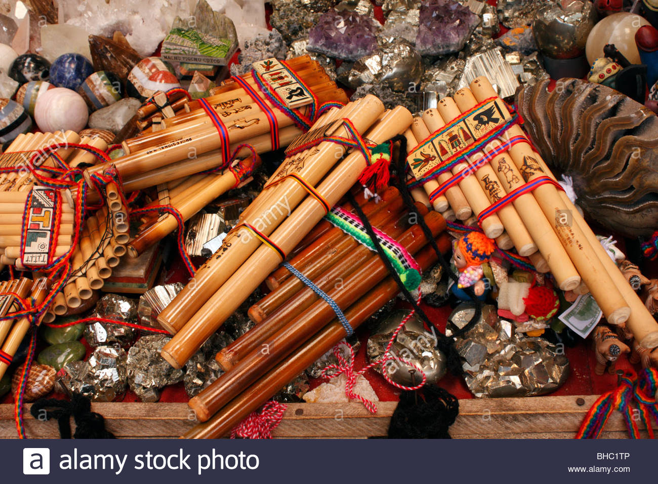 Andean pipes ('pan pipes') with mineral specimens on a souvenir stall in a market by Aguas Calientes railway - Stock Image