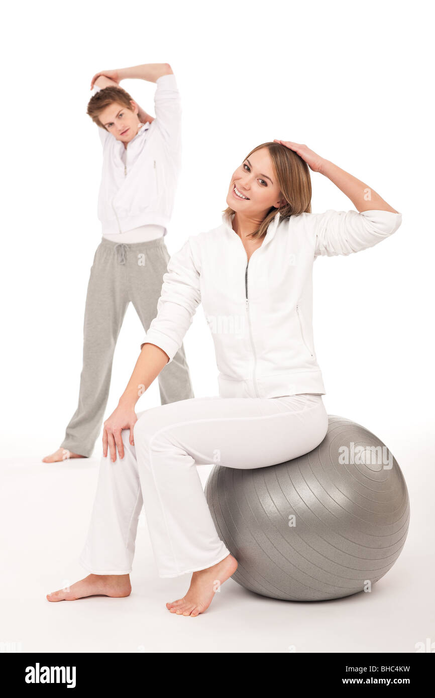 Fitness - Healthy couple stretching after training on white background - Stock Image