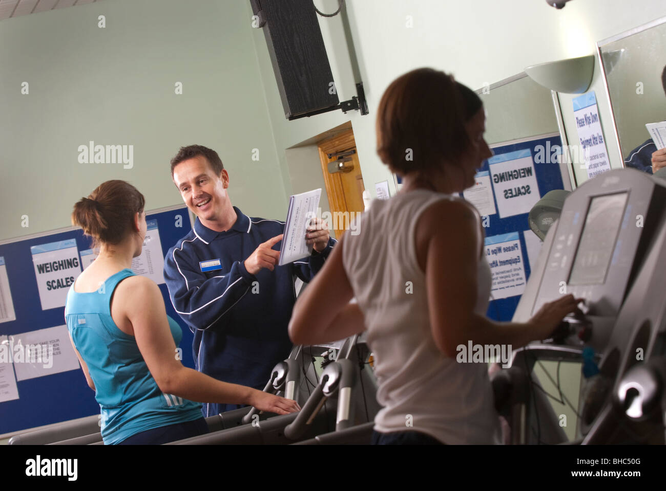 Personal trainer gives an introduction to someone on a treadmill UK - Stock Image