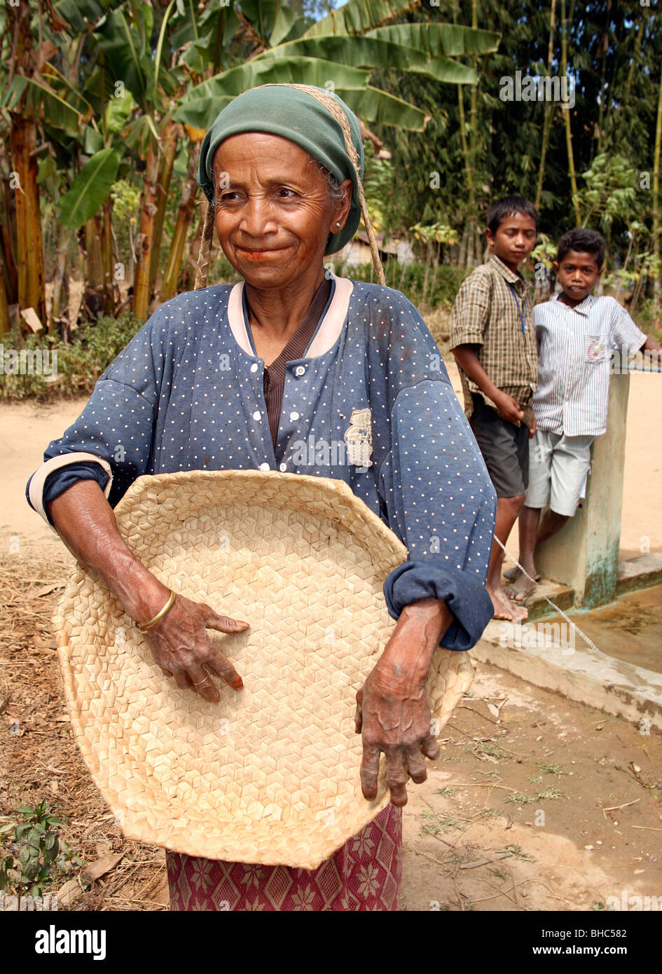 Respected elderly hard working woman farmer with her rice gleaning basket at Elcolbere village Alieu region EastTimor Stock Photo