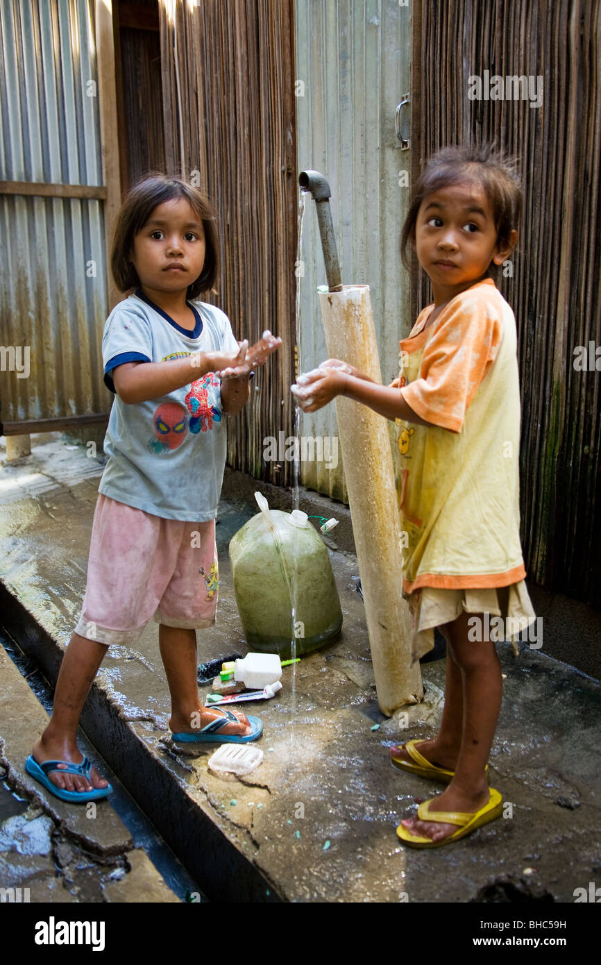 Girls washing at Dili Hospital IDP camp where toilets and water installed by Oxfam  in East Timor - Stock Image