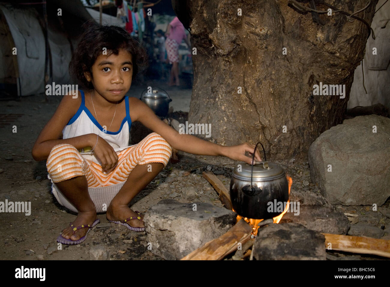 Young woman with cooking pot on open fire prepares a meal in crowded IDP camp for displaced homeless families in Stock Photo