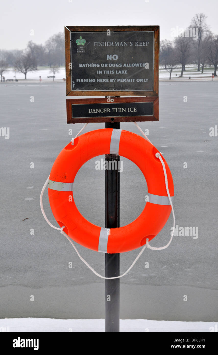 Lifebelt and warning sign, Serpentine, Hyde Park, London W2, United Kingdom - Stock Image