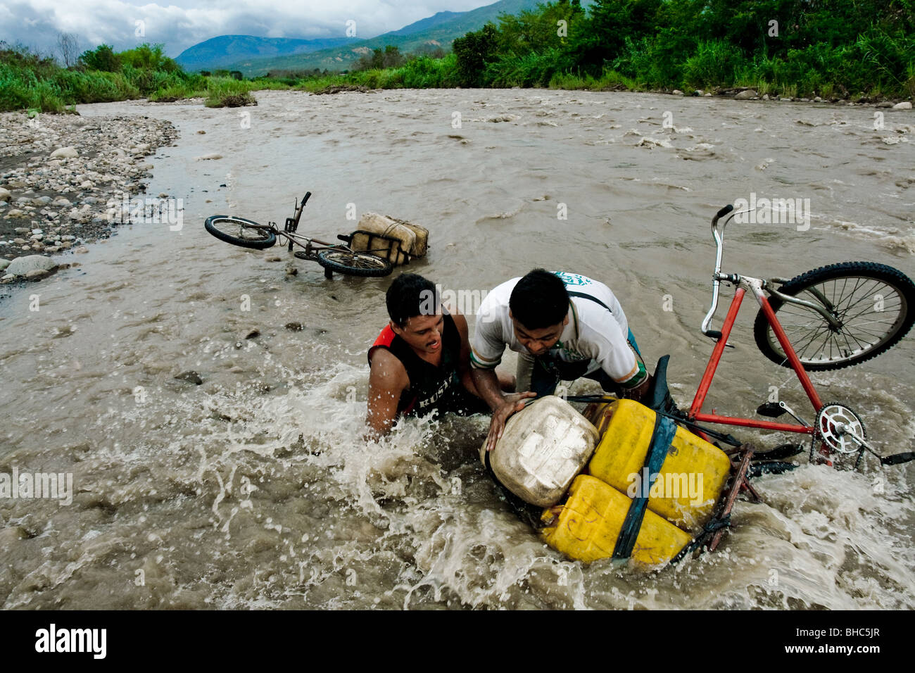 Gasoline smugglers with their contraband fell into the water of the river Táchira on the Colombian-Venezuelan - Stock Image