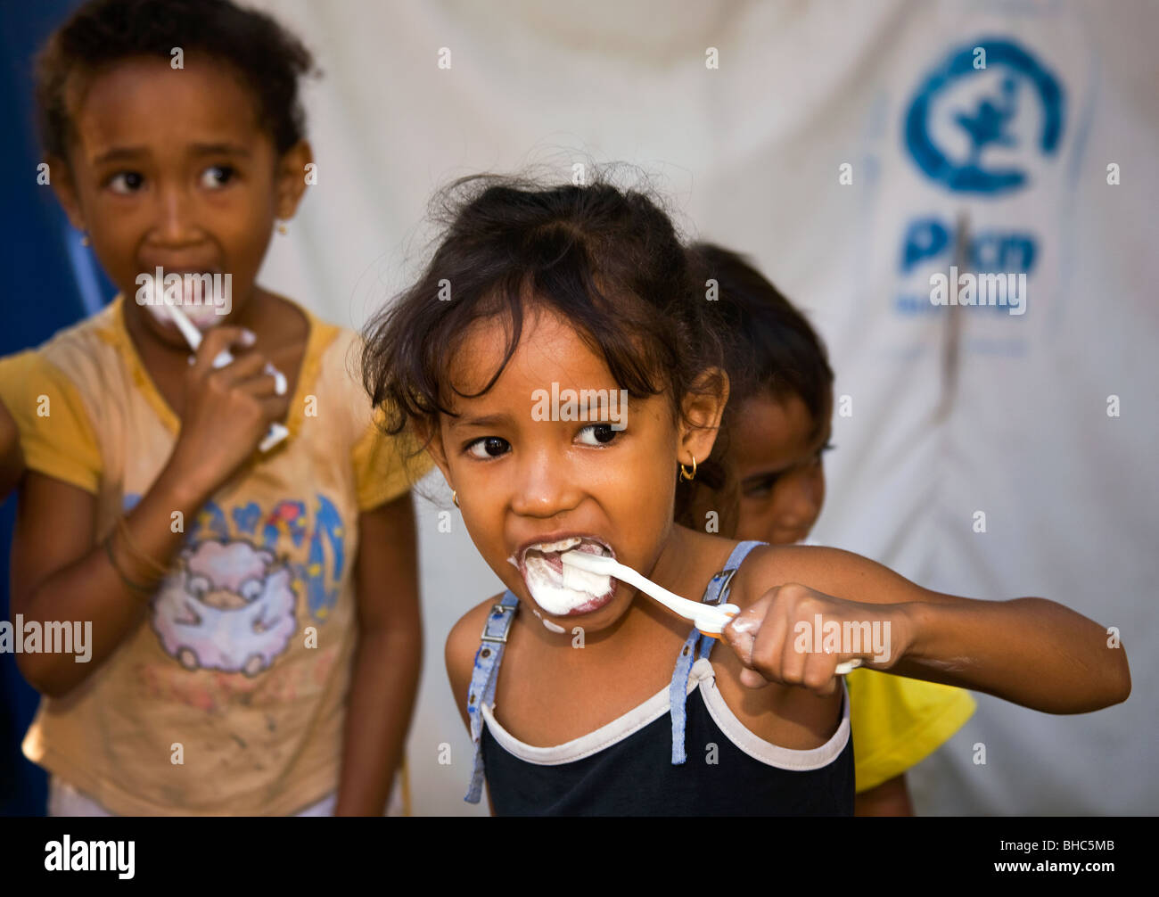 Cleaning teeth PLAN provide water sanitation toothbrushes toothpaste for children at IDP displaced persons camp Stock Photo