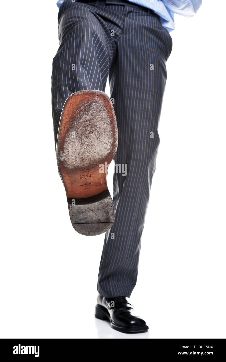 The leather sole of a mans shoe as he is about to step on something, - Stock Image