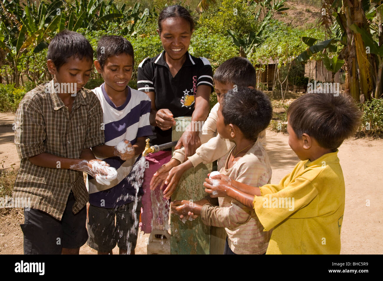 Boys shown how to use soap to wash under tap-water for first time in remote Elcolbere village East Timor - Stock Image